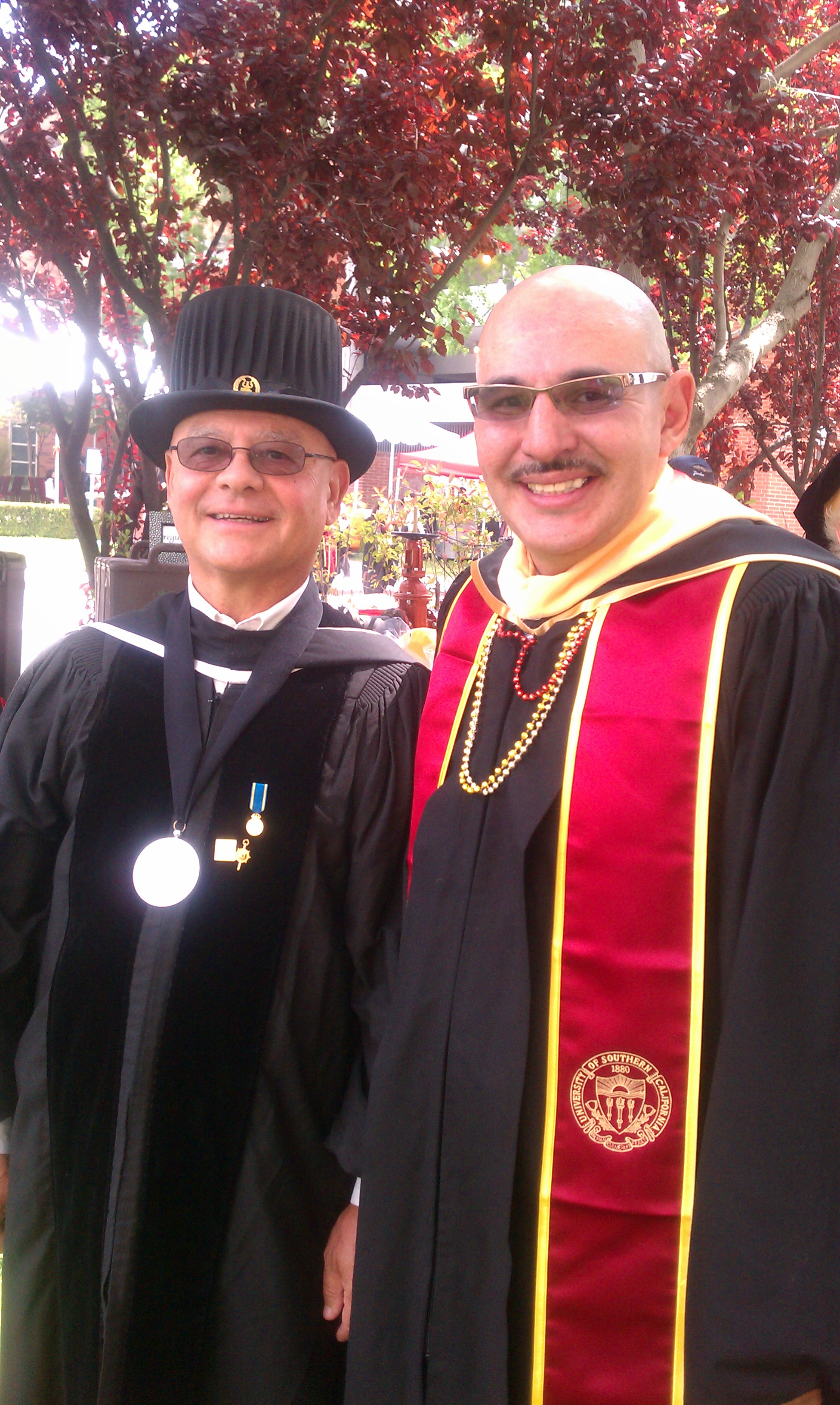 Ray Zacarias on right in gradudation cap and gown from USC