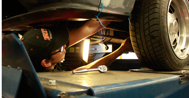 student working underneath car