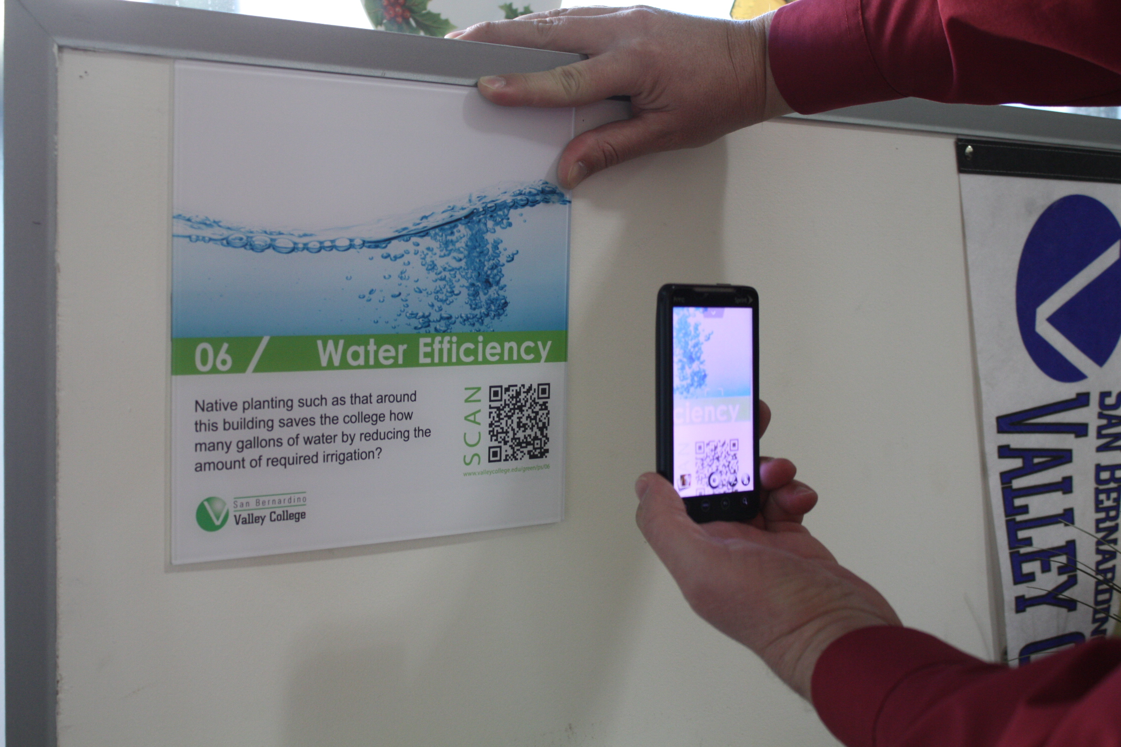 picture of person using smartphone to scan QR code on LEED sign