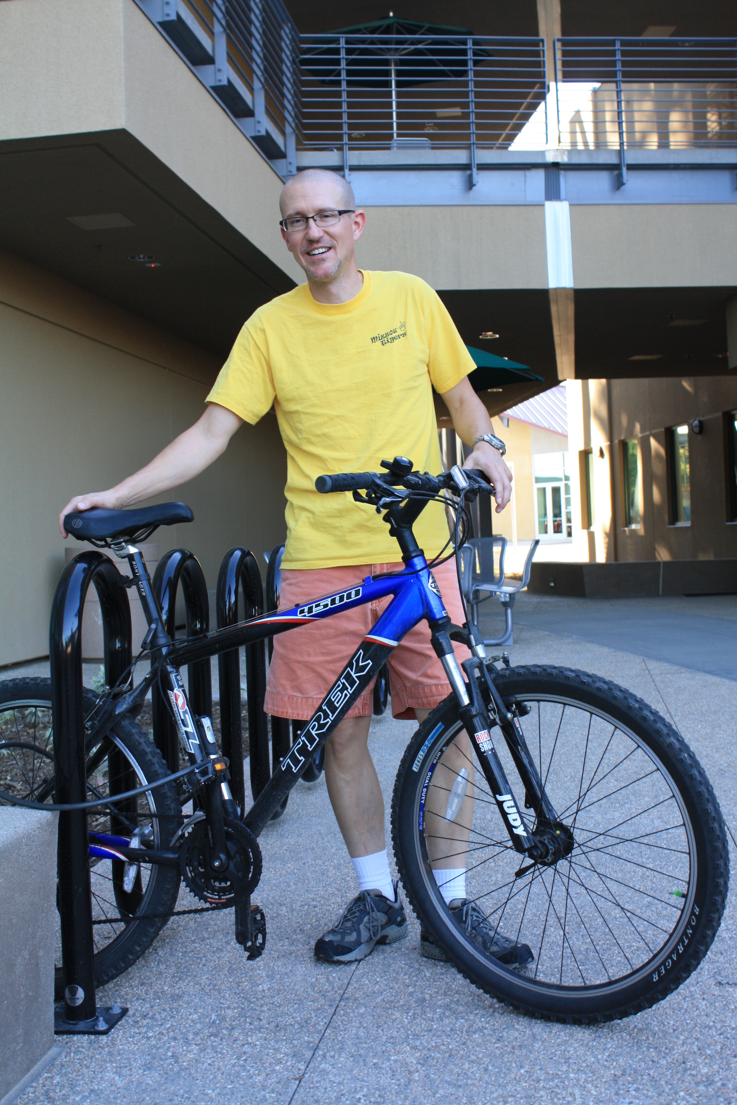 Professor Todd Heible poses with his bicycle in front of the bike rack outside the PS building