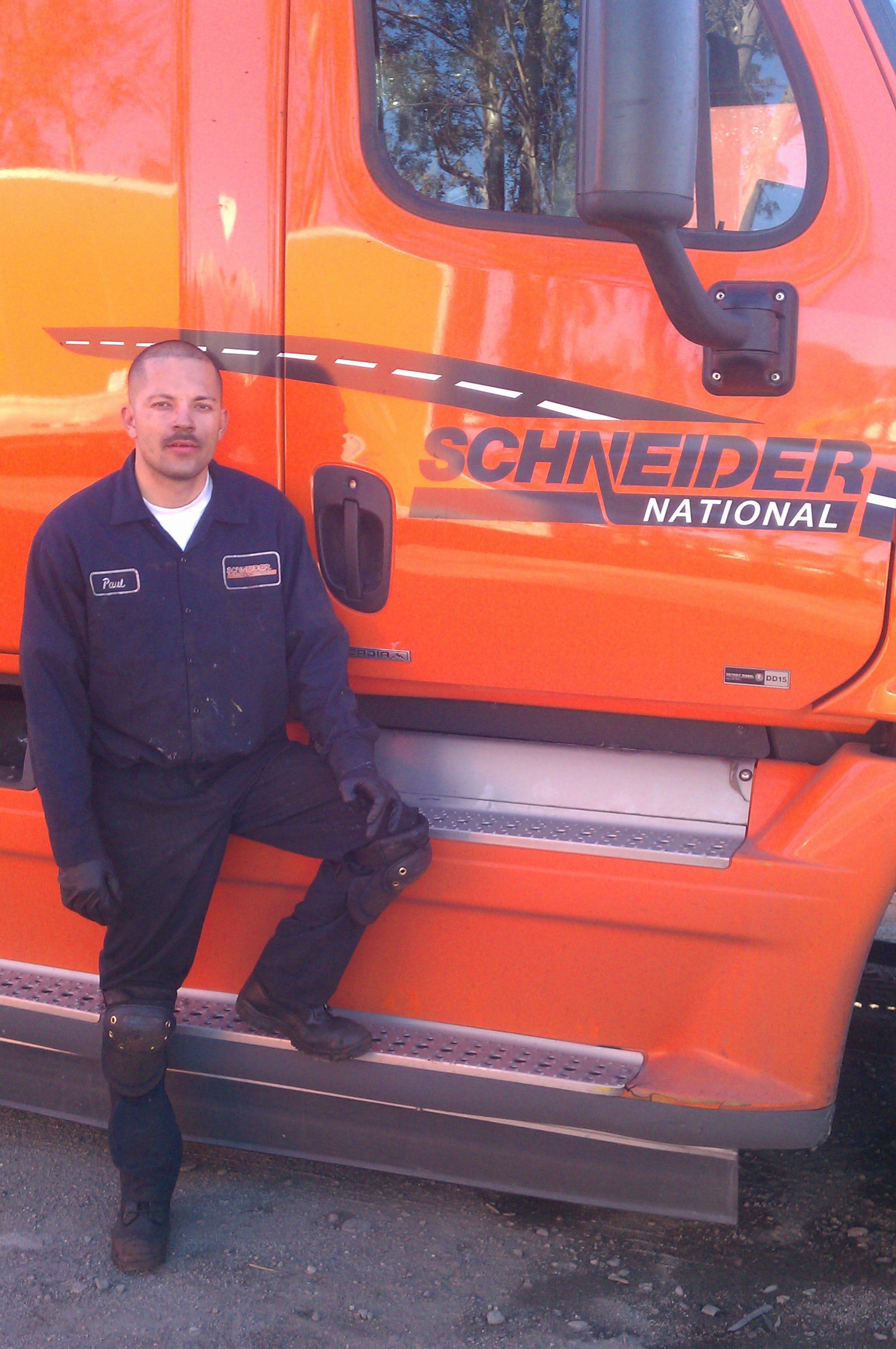 student paul prado poses next to an orange schneider semi-truck